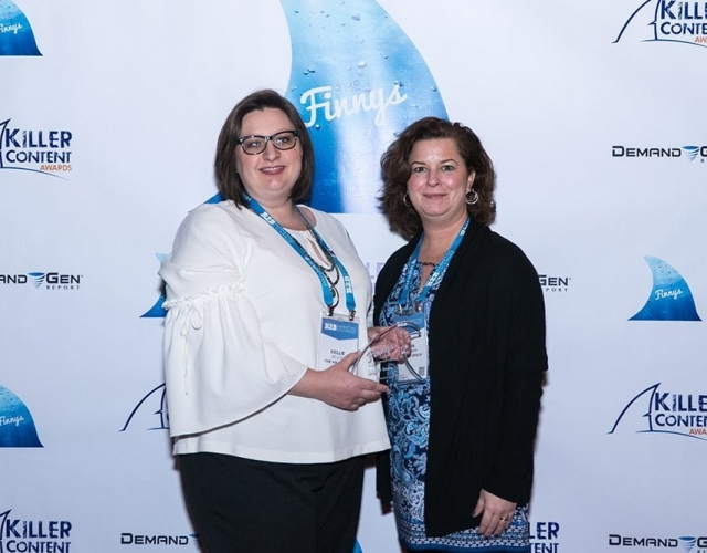 Kellie De Leon and Nina Kuhlman of The Mx Group accept the Finny award for the Sales Enablement Campaign category on behalf of winner Temper Sealy Hospitality.